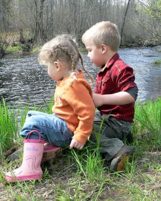 Bode and Courtney enjoy watching flowers float down the river.